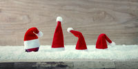 Four red Santa Claus hats and white snow .