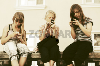 Group of teen girls calling on mobile phones against a school building