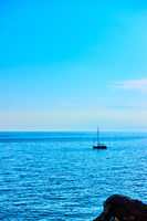 Minimalistic seascape with small sail yacht