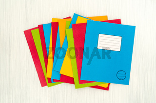 Colored exercise books on wooden table