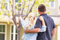 Happy Caucasian Couple Facing and Pointing to Front of House