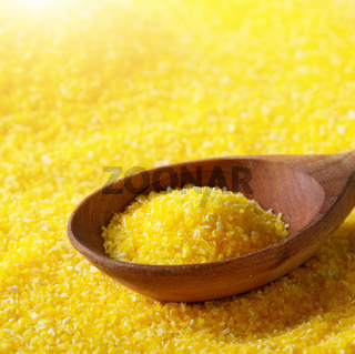 Corn grits yellow background with wooden spoon