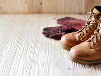 Yellow leather used work boots and protective gloves on wooden background closeup. Place for text