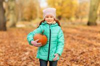 happy little girl with pumpkin at autumn park