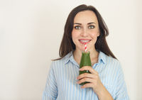 Healthy woman posing with fresh juice bottle of green detox smoothie. Happy beautiful fit girl with fresh juice