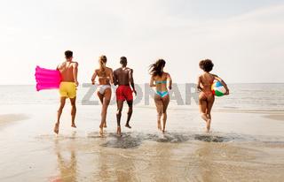 friends run with beach ball and swimming mattress