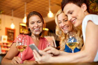 women with smartphone at wine bar or restaurant
