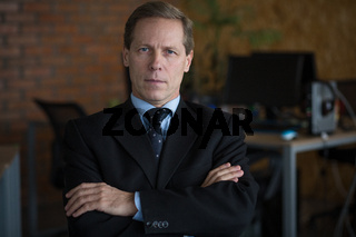 Confident business man posing at camera. He is looking at camera and standing with his arms crossed.