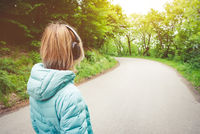 Portrait of an attractive athletic blonde girl from back to light running down jacket, wearing bluetooth headphones with music or nature sounds when on a forest road