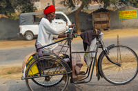 Indian man riding a tricycle