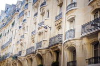 Paris old building with straight and round balconies, awnings, stucco