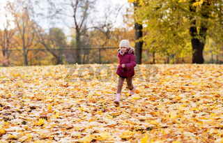 happy girl running at autumn park