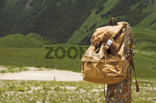 Hipster yellow vintage backpack with a mug fixed on it with a mug close-up front view. Traveler's travel bag in the background of a mountain landscape