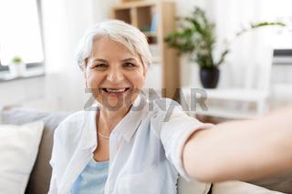 smiling senior woman taking selfie at home