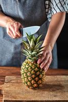 Woman's hands with a knife cut a juicy pineapple on a wooden board on a brown table around a dark background. Healthy ingredient