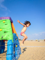 The little girl jump from a colorful toy house