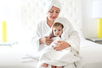 Young woman in the room with baby after bath