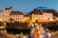 View of lively river Ljubljanica bank in old city center decorated with Christmas lights at dusk. Old medieval Ljubljana cstle on the hill obove the city. Ljubljana, Slovenia, Europe