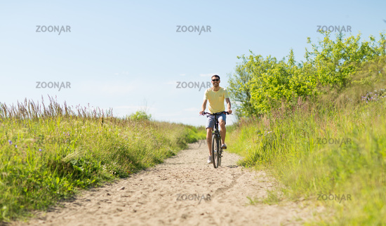 happy smiling man riding bicycle outdoors