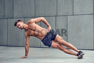 Fit healthy man doing side planks