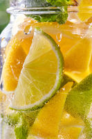 Cold refreshing water with lime and lemon in a glass.