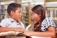 Hispanic Boy and Girl Having Fun Studying Together In The Library