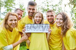 Junges Start-Up Team mit einem Teambuilding Schild