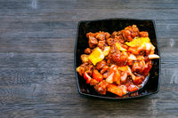 Pork in sweet and sour sauce in bowl on dark board