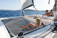 Beautiful woman relaxing on a summer sailing cruise, lying and sunbathing in hammock of luxury catamaran sailing around Maddalena Archipelago, Sardinia, Italy in warm afternoon light