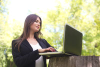 Business woman with laptop in park