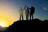 travelers making high five over sunrise