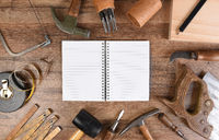 High angle closeup of a large group of tools arranged around an open note book with blank pages