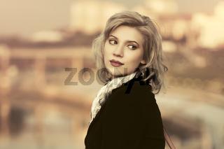 Fashion blond woman in black coat walking in city street