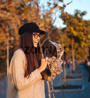 Beautiful young girl with handbag posing on camera