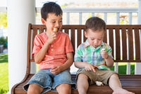 Young Mixed Race Chinese and Caucasian Brothers Enjoying Their Ice Cream Cones