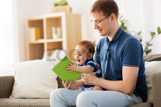 happy father and little baby son with book at home