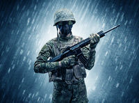 Armed soldier standing in rainy weather