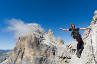 young attractive blonde female mountain climber in the Dolomites of Italy waving and smiling