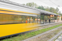 A yellow tram in motion