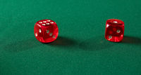 Red gambling dices on green table