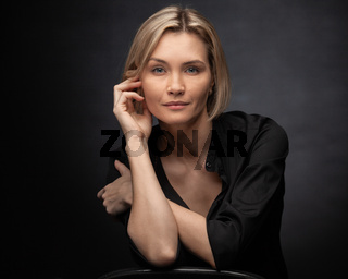 Beautiful middle-aged woman on a gray background in a black blouse.