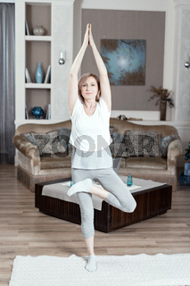 A 50 Year Old Woman Practices Yoga at Home in the Living Room.