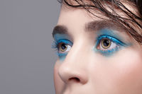 Closeup macro portrait of female face. Woman with unusual beauty makeup and wet hair, and blue shadows make-up.