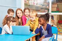 Kinder und Lehrerin zusammen am Laptop