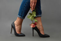 In the hand of a stylish girl a pink rose, a girl's legs in jeans and black high-heeled shoes around a dark background with copy space.
