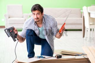 Man laying flooring at home
