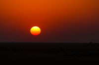 The sun sets over the horizon in the desert