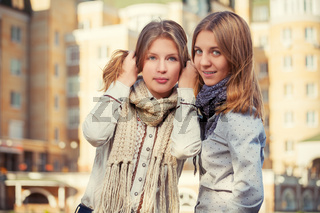 Two young fashion girls in white shirt and scarf walking in city street