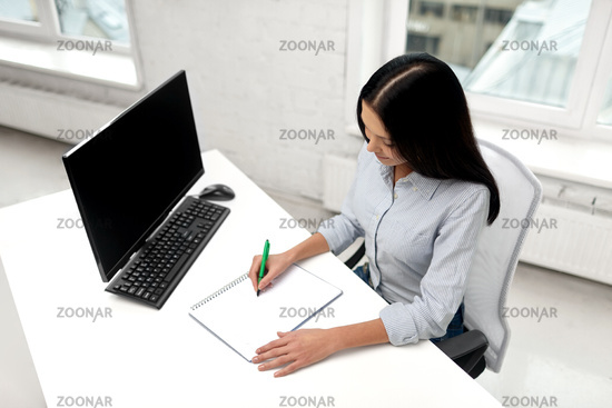 businesswoman writing to notebook at office