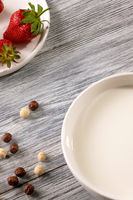 Ripe strawberries, cereal balls and a plate of milk on a gray wooden table. Top view
